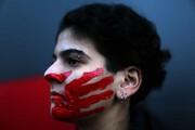 عکس روز: دست سرخ روی صورت زن
