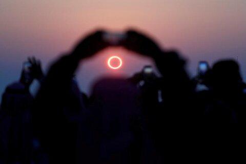 مردم در هفاف در شرق عربستان با گوشی از خورشیدگرفتگی عکس میگیرند