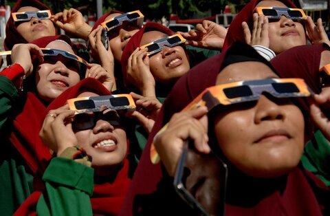 زنان با عینک محافظ در گووا در اندونزی خورشیدگرفتگی را میبینند
