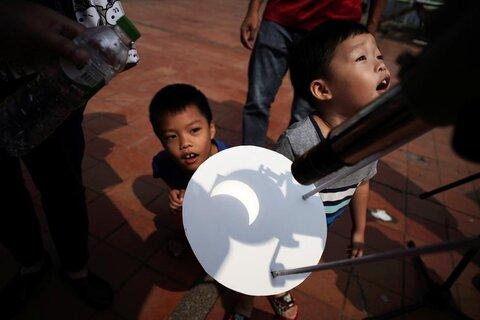 مردم در «مرکز آموزش علمی» در بانکوک پایتخت تایلند خورشیدگرفتگی نسبی را مشاهده میکنند