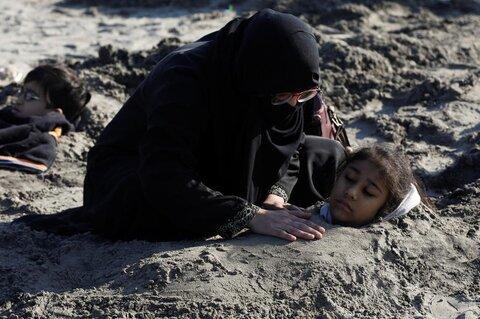 زنی در ساحلی در کراچی پاکستان دخترش را برای شفای معلولیتش در هنگام خورشید گرفتگی تا گردن در شن فرو کرده است.
