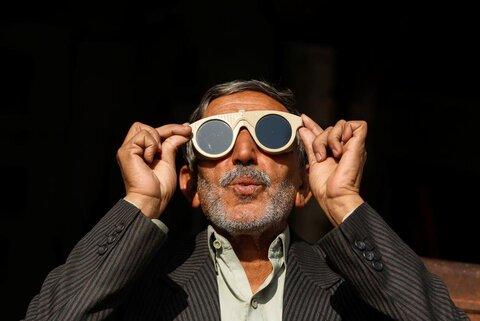 مردی در پیشاور پاکستان با عینک جوشکاری به خورشیدگرفتگی نگاه میکند