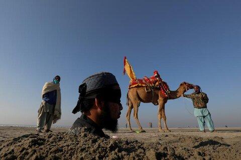 مردی در کراچی پاکستان در جریان خورشیدگرفتگی با چشمهای بسته تا گردن در شن فرو برده شده تا به باور محلی شفا بگیرد