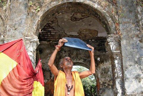 یک روحانی هندو خورشیدگرفتگی جزئی را در بیرون معبدی آگارتالای هند با یک فیلم رادیوگرافی سیاهشده میبینید
