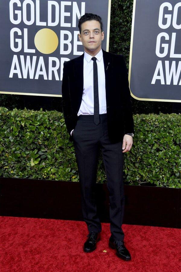 رامی ملک یککت مخمل مشکی و پیراهن اسکینی سفید با شلوار مشکی و یک کراوات باریکاز برند ایوسن لورن پوشیده بود.