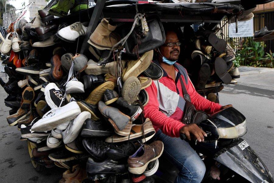 پنومپن/ ویتنام. فروشنده کفشهای دست دوم در راه بازار