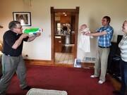 عکس | ابتکار جالب یک کشیش؛ غسل تعمید با تفنگ آبپاش