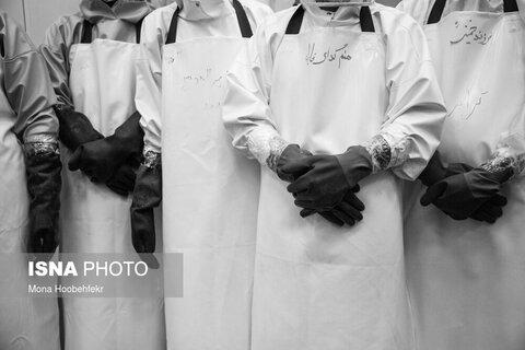 تعدادی از کسانی که برای غسل اموات کرونایی داوطلب شدهاند. بر روی لباسهای مخصوص خود شعارهایی را نوشتهاند.