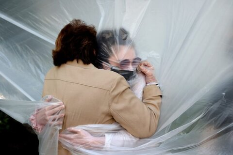 در آغوش كشيدن مادربزرگ به واسطه پوششي پلاستيكي