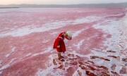عکس روز | دختر قرمز دریاچه صورتی