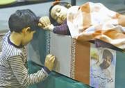 عکس | خواب آرام دختر روی تابوت پدر