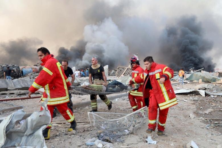 آتشنشانان در بندر بیروت در حال انتقال مصدومان