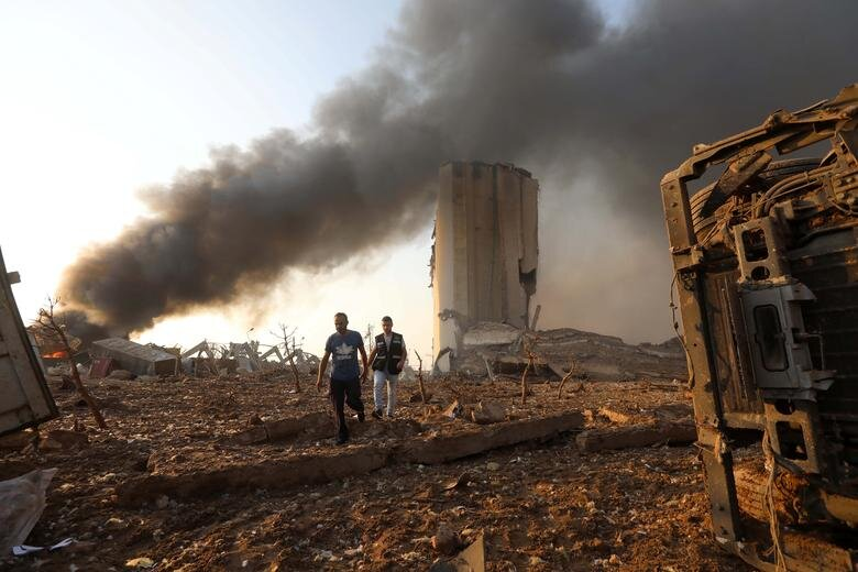 مردان در حال راه رفتن در محوطه انفجار در بیروت
