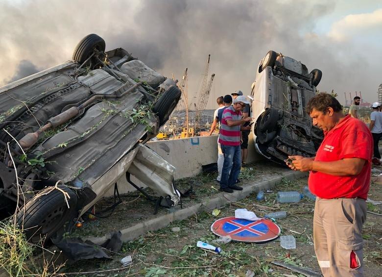 مردم در کنار خودروهای آسیب دیده از انفجار در بیروت