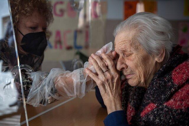 یکی از ساکنان یک خانه سالمندان در دوران شیوع کرونا در رم با دخترش ملاقات میکند./ ایتالیا