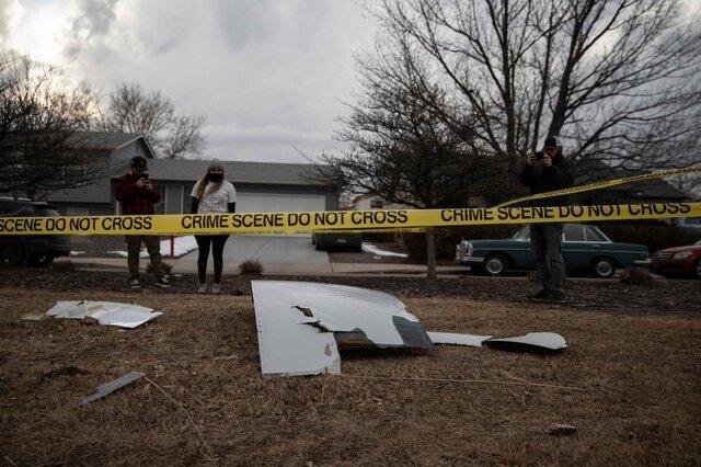 ساکنان منطقه «برومفیلد» از تکههایی که از موتور یک هواپیما به زمین افتاده است عکسبرداری میکنند. این تکههای عظیم از هواپیمای درحال پروازی که به دلیل نقص فنی ناچار به بازگشت به فرودگاه «دنور» شده بود به زمین سقوط کرده است./ کلرادو / ایالات متحده آمریکا