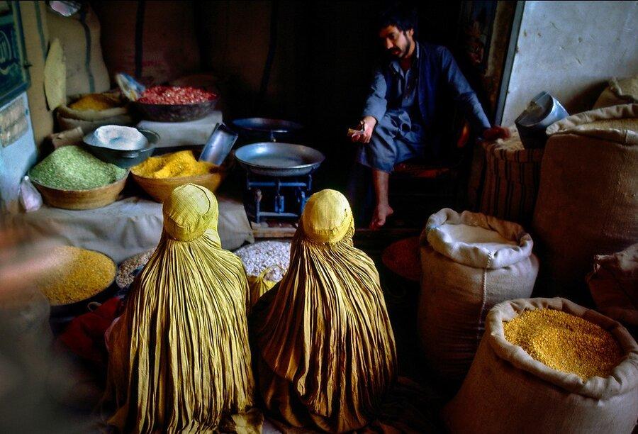 زنان افغان با برقع زرد در مغازه عطاري مشغول خريد هستند.