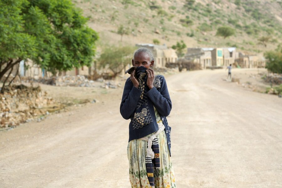 زنی روستانی بینی خود را پوشانده تا بوی اجساد سوخته را کمتر حس کند
